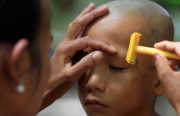 A boy gets his head shaved by his mother during an ordination ceremony. Kork Banteay village, Kandal province. Copyright Heng Sinith/AP