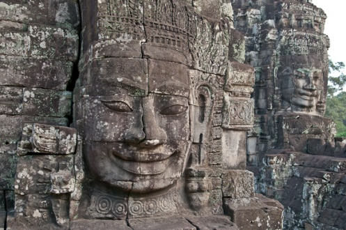 Faces of the Bayon temple, Angkor. The central tower contains a shaft from the summit to ground level, and when archaeologists explored this they found at the bottom a shattered statue of a multi-headed naga sheltering the Buddha.